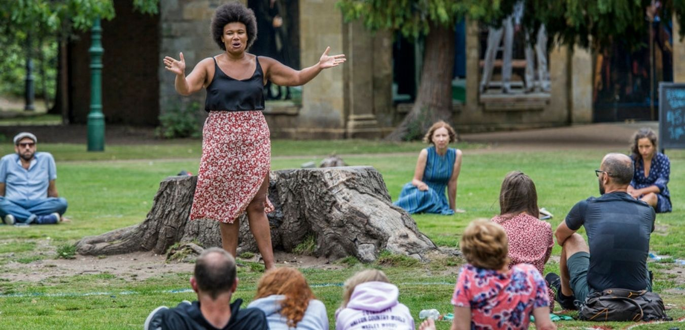 Actor performing outside to socially distanced audience