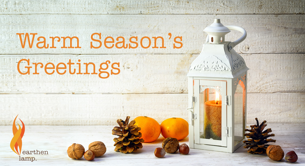 White lantern on table with fir cones. Text reads Warm Season's Greetings